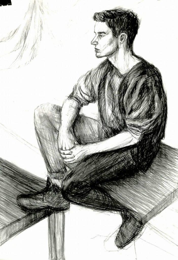 rysunek młody mężczyzna na stole